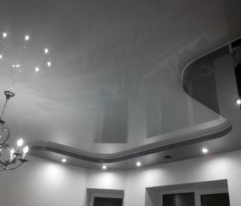 Серый натяжной глянцевый потолок в спальню