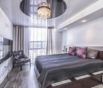 Серый натяжной глянцевый потолок спальная комната